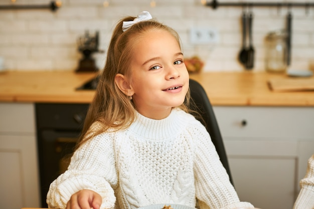 Isoliertes bild des entzückenden kleinen mädchens mit weißem band in ihrem haar, das zu hause gegen unscharfes kücheninnere aufwirft