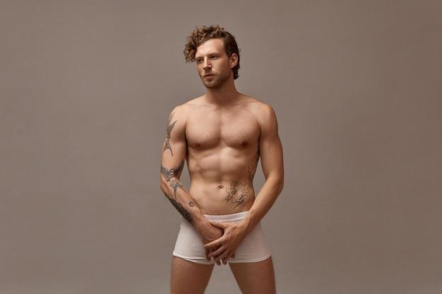Isoliertes bild des herrlichen gutaussehenden mannes mit stoppeln und der lockigen frisur, die nackt posiert, nur weiße boxershorts tragend, beide hände auf leistengegend haltend, ernsthaften gesichtsausdruck habend