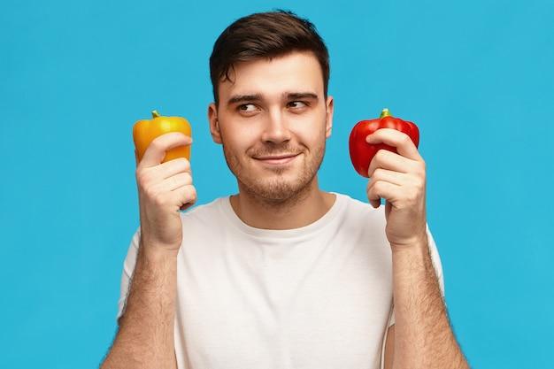 Isoliertes bild des niedlichen attraktiven jungen mannes, der nachdenklichen geheimnisvollen gesichtsausdruck hat, wegschaut, zwei paprika hält, überlegt, was für vegetarisches abendessen zu kochen oder zu vergleichen
