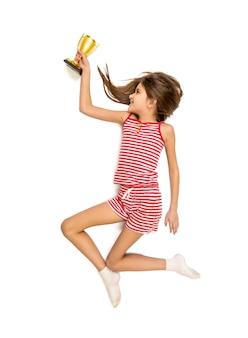 Isoliertes foto eines glücklichen mädchens, das mit goldenem pokal läuft