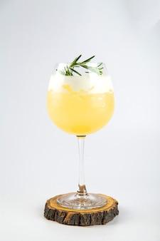 Isoliertes glas des gelben cocktails mit rosmarin