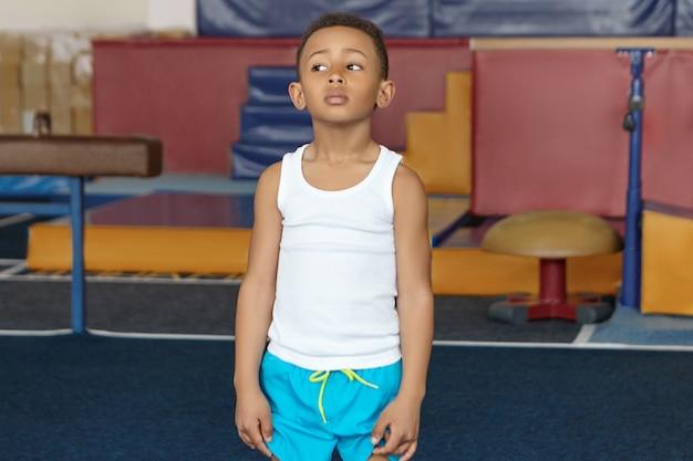 Isoliertes innenporträt des hübschen niedlichen schwarzen dunkelhäutigen schuljungen im weißen t-shirt und in den blauen shorts