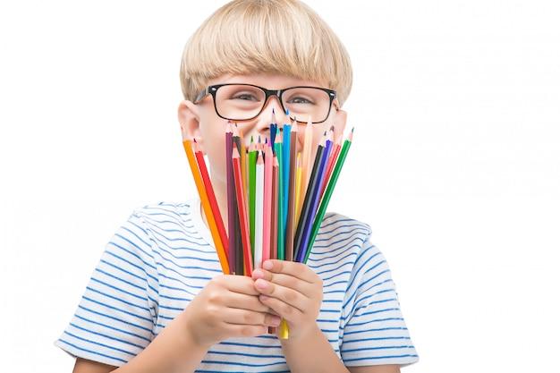 Isoliertes kind mit stiften. entzückendes kind auf weißem hintergrund. porträt des lustigen blonden jungen mit bunten stiften.