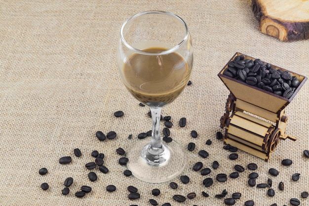 Isoliertes konzept des kolumbianischen kaffees mit einer mahlmaschine und kaffeebohnen und einer tasse kaffee-crema