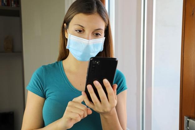 Isoliertes mädchen mit maske und smartphone zu hause.
