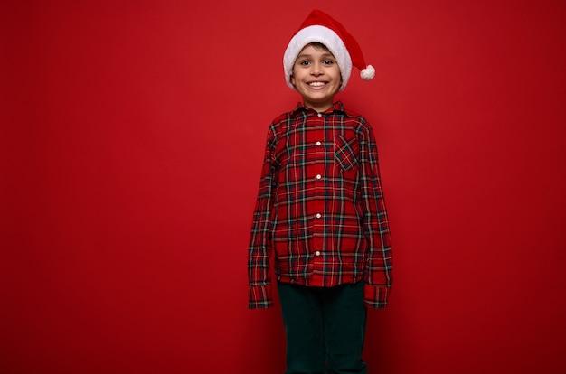 Isoliertes porträt auf farbigem hintergrund mit kopienraum für weihnachten und neujahrsanzeige eines fröhlichen lustigen süßen vorjugendlichen jungen in rotem kariertem hemd und grüner samthose, der in die kamera schaut