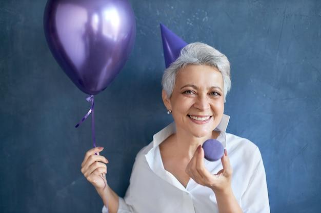 Isoliertes porträt der fröhlichen entspannten reifen frau im weißen hemd, das breit an der kamera lächelt und heliumballon hält