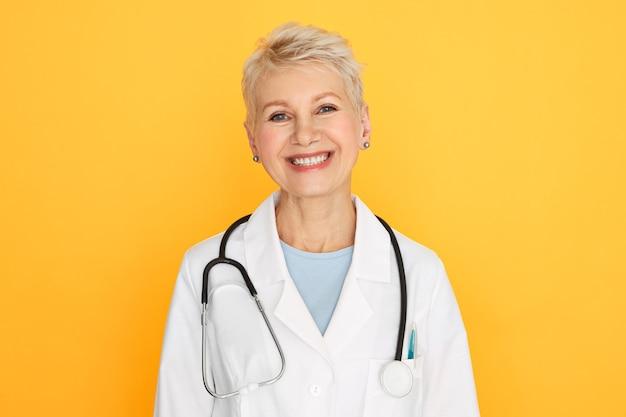 Isoliertes porträt der selbstbewussten erfahrenen ärztin mittleren alters mit kurzem blondem haarschnitt, der mit glücklichem lächeln schaut