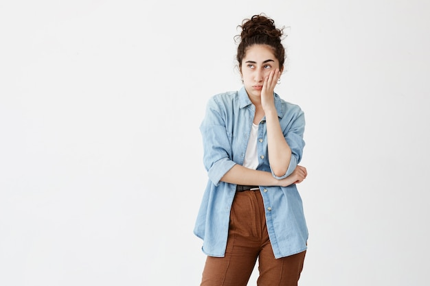 Isoliertes porträt der stilvollen jungen frau mit dunklem haar im brötchen im jeanshemd, das ihr kinn berührt und mit zweifelhaftem und skeptischem ausdruck seitwärts schaut und wichtige lebensentscheidung trifft.