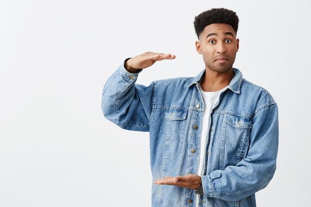 Isoliertes porträt des jungen lustigen dunkelhäutigen mannes mit afro-frisur im lässigen weißen hemd unter jeansjacke, die vorgibt, große kiste in händen mit aufgeregtem gesichtsausdruck zu halten