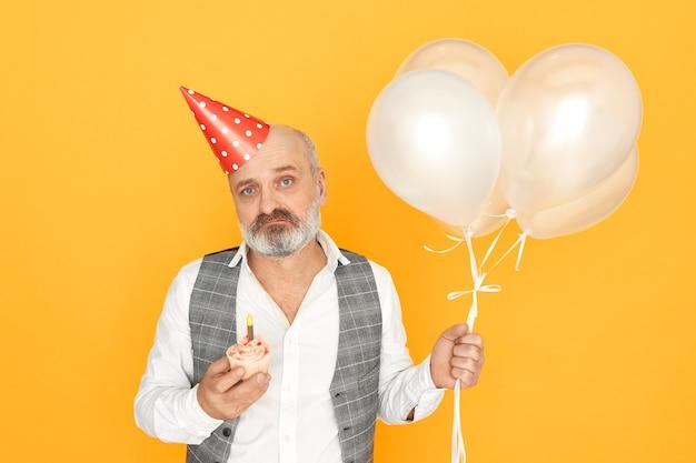 Isoliertes porträt des unglücklichen unrasierten männlichen rentners mit kegelhut auf seinem kahlen kopf, der niedergedrückt wird, alt wird, luftballons und cupcake hält