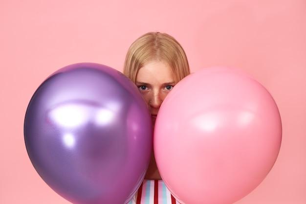 Isoliertes porträt einer mysteriösen jungen blonden frau mit sommersprossen und piercing im gesicht, die auf rosa posiert und sich hinter zwei glänzenden metallischen heliumballons versteckt
