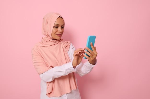 Isoliertes porträt einer selbstbewussten arabisch-muslimischen frau mittleren alters in strengem religiösem outfit und bedecktem kopf in rosa hijab, die eine nachricht auf einem mobiltelefon in ihren händen schreibt, farbiger hintergrund, kopierraum