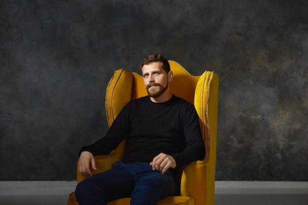 Isoliertes porträt eines gut aussehenden eleganten jungen europäischen mannes mit unscharfem bart und schnurrbart, die stilvolle schwarze kleidung tragen, die allein im bequemen gelben sessel sitzend aufwirft