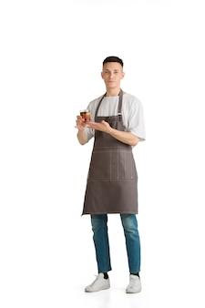 Isoliertes porträt eines jungen männlichen kaukasischen barista oder barkeeper in brauner schürze lächelnd