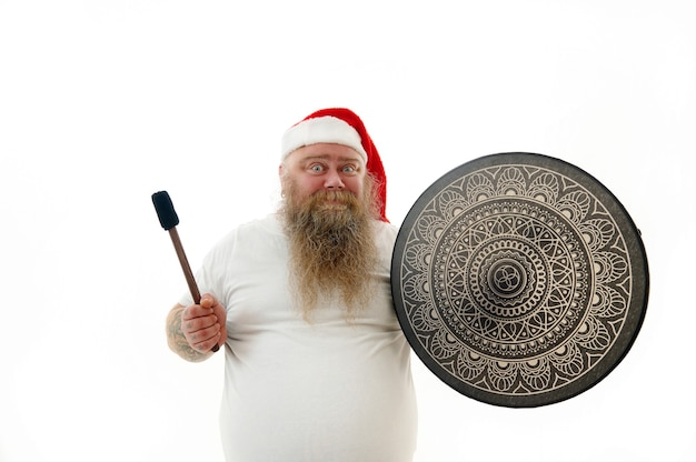 Isoliertes porträt eines überwiegenden lächelnden schamanen mit tätowierten armen im weihnachtsmannhut, der ein schamanen-tamburin hält, das emotion ausdrückt.