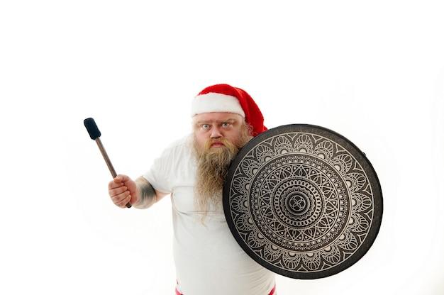 Isoliertes porträt eines wütenden und ernsten überwiegenden mannes i weihnachtsmannhut, der mit einem schamanen-tamburin tanzt. emotion: wut