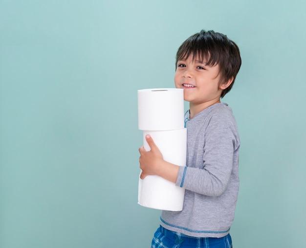 Isoliertes seitenansichtporträt des niedlichen kindes, das toilettenrolle auf blauem hintergrund hält, kinderjunge mit lächelndem gesicht, während ein stapel toilettenpapier trägt