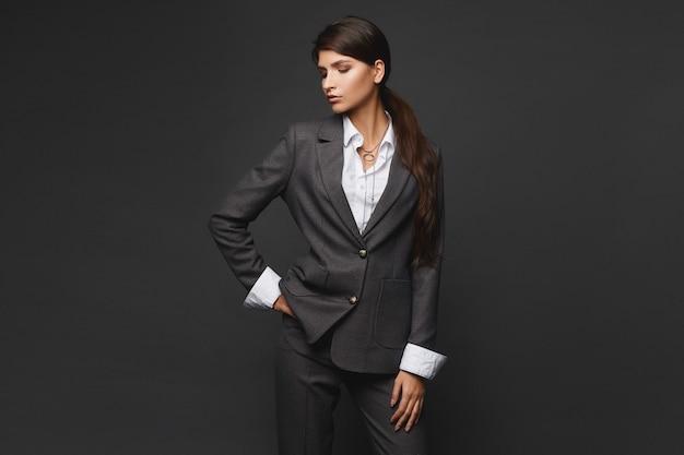 Isoliertes studioporträt einer selbstbewussten geschäftsfrau in einem grauen, stylischen anzug