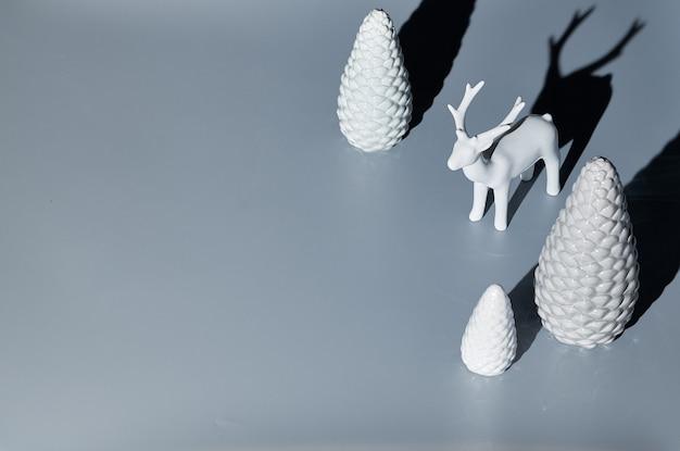 Isometrische weihnachtsanordnung mit keramikhirsch- und weihnachtsbaumschmuck. minimalistisches langes schatten-design. schwarzweißbild mit kopierraum