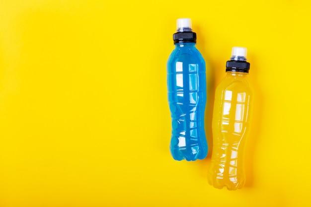 Isotonisches energiegetränk. flasche mit blauer und gelber transparenter flüssigkeit, sportgetränk
