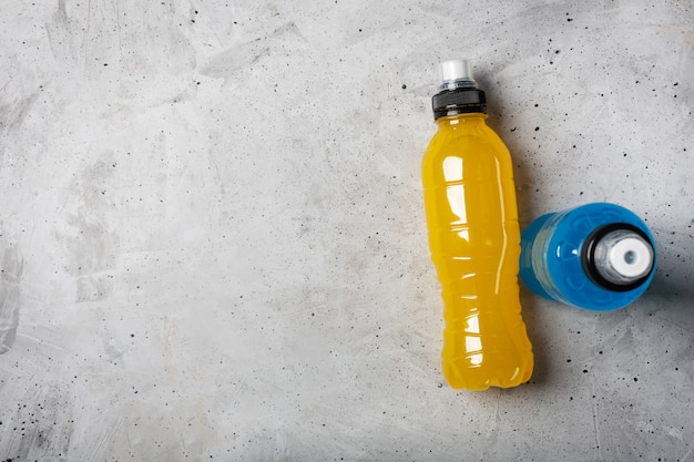 Isotonisches energiegetränk. flaschen mit blauer und gelber transparenter flüssigkeit