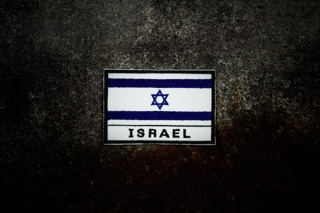 Israel-flagge auf rostigem verlassenem metallboden in der dunkelheit.