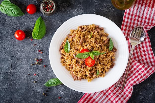 Israelischer couscous mit rindfleisch. leckeres essen. asiatische mahlzeit draufsicht flach legen