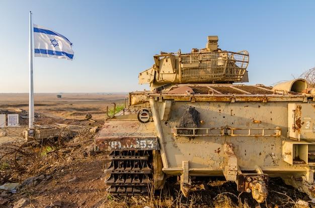 Israelisches flaggenfliegen neben einem außer dienst gestellten israelischen zenturio-panzer in israel