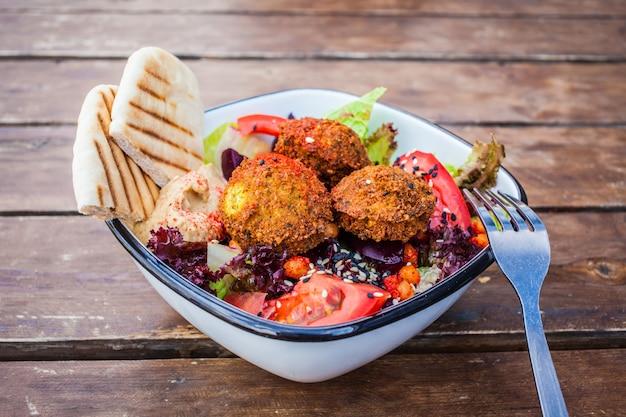 Israelisches straßenessen. falafel-salat mit hummus, rote-bete-wurzeln und gemüse in der schüssel in einem restaurant.