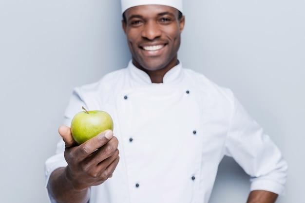 Iss eine gesunde mahlzeit! glücklicher junger afrikanischer koch in weißer uniform, der grünen apfel ausstreckt