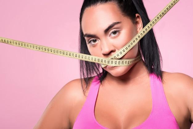 Iss oder werde fett. nahaufnahme der hübschen mulattin, die ihren mund mit körpermaßband bedeckt