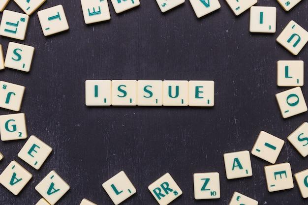Issue scrabble-briefe über schwarzem hintergrund angeordnet