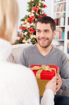 Ist das für mich? fröhlicher junger mann, der auf der couch sitzt und eine geschenkbox von seiner freundin erhält, die in seiner nähe sitzt