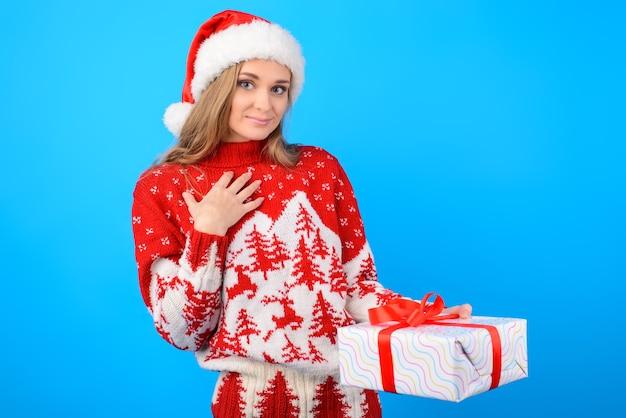 Ist das für mich? glückliche aufgeregte freudige frau im warmen strickpullover erhält eine geschenkbox, lokalisiert auf lebendigem blauem hintergrund