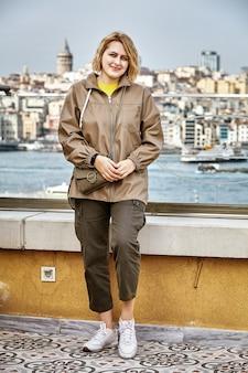 Istanbul-stadtbild und goldene hornbucht hinter dem rücken der jungen weißen frau, die auf der reise posiert