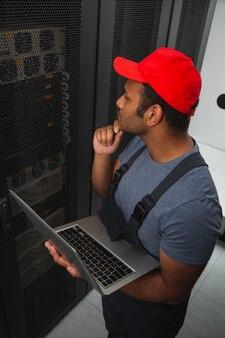 It-herausforderungen. draufsicht des nachdenklichen it-ingenieurs, der kinn berührt und laptop hält