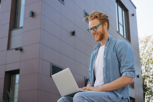 It-spezialist programmiert mit einem laptop, der von zu hause aus arbeitet