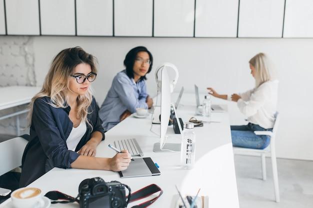 It-spezialistin, die an einem projekt arbeitet, das mit internationalen kollegen im büro sitzt