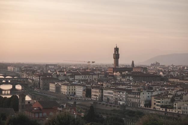 Italien auf einer langfokuslinse, blick vom spielplatz am arno und auf den palazzo vecchio bei sonnenuntergang am abend.