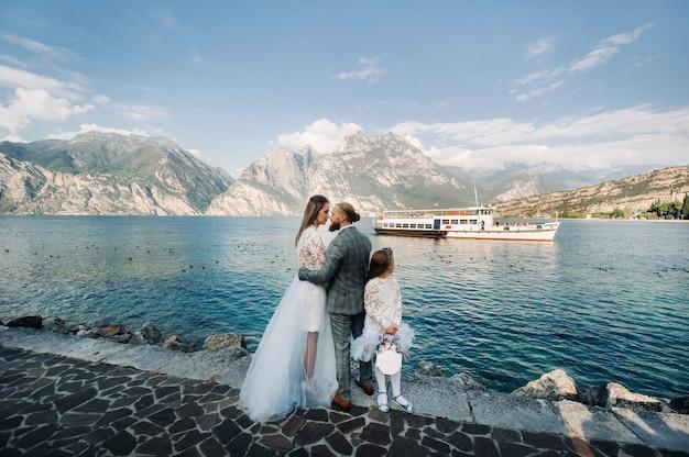 Italien, gardasee. schöne familie am ufer des gardasees in italien am fuße der alpen. vater, mutter und tochter in italien.