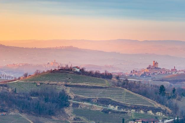 Italien piemont: weinberge einzigartige landschaft bei sonnenuntergang, mittelalterliche burg serralunga d'alba auf hügel