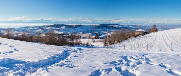 Italien piemont: weinbergreihe, einzigartige landschaft im winter mit schnee, ländliches dorf auf einem hügel