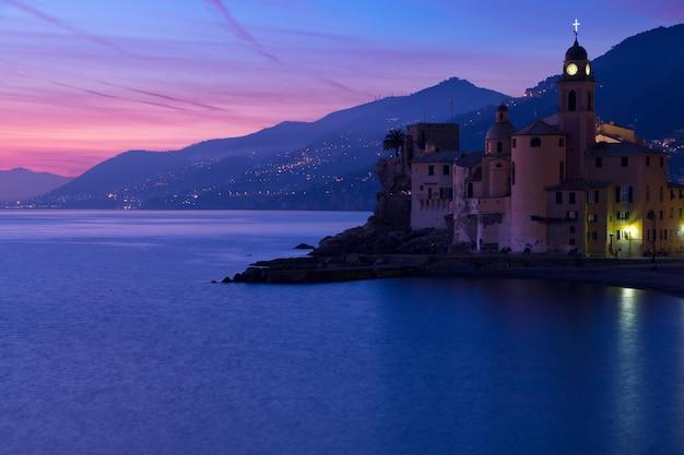 Italien. stadt camogli. mittelmeer. blick auf berge, meer, strand und stadtuhr. nach sonnenuntergang