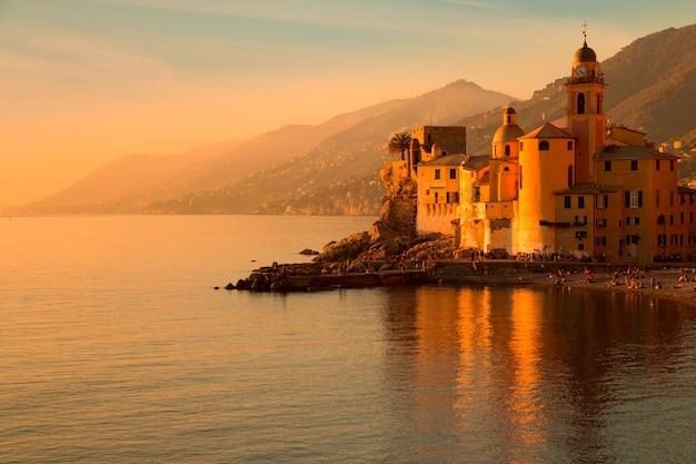 Italien. stadt camogli. mittelmeer. blick auf berge, meer, strand und stadtuhr. schöner farbiger sonnenuntergang