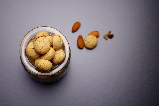 Italienische amaretti-kekse in einem glas auf einem grau. Premium Fotos