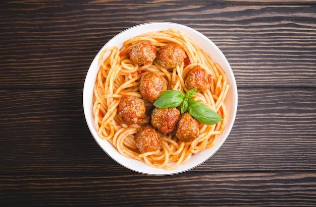 Italienische amerikanische traditionelle gerichtsspaghetti mit fleischbällchen, tomatensauce und basilikum in der schüssel, rustikaler hölzerner hintergrund.