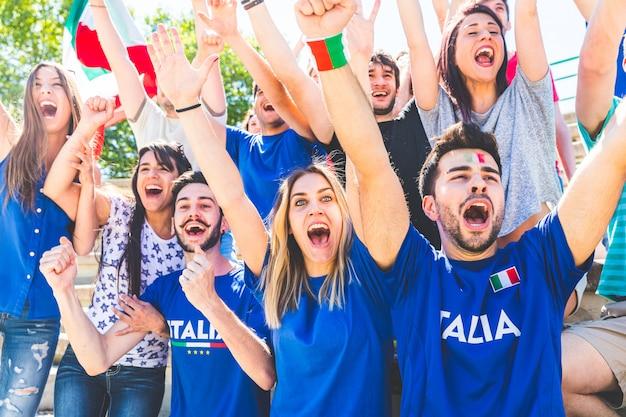 Italienische anhänger, die am stadion mit flaggen feiern