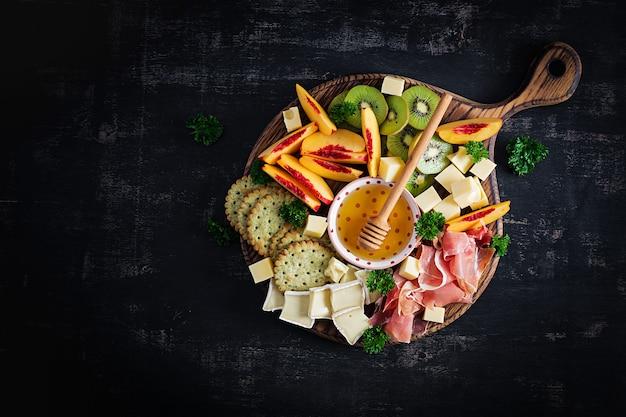 Italienische antipasti-catering-platte mit schinken, käse und obst auf dunklem hintergrund. draufsicht, überkopf