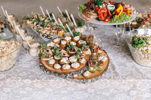 Italienische antipasti-wein-snacks set brushettas käsesorte mediterrane oliven gurken prosciutto di parma mit melonensalami und wein in gläsern über schwarzem grunge-hintergrund draufsicht
